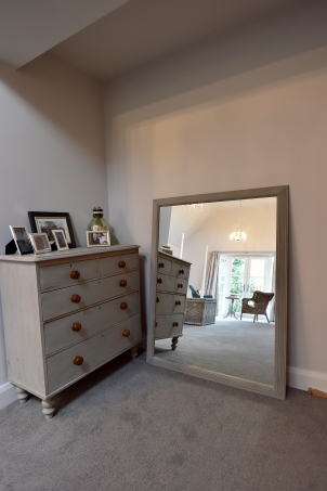 Large mirror and chest of drawers in master bedroom