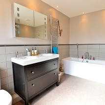 A family bathroom with plenty of storage and functional lighting.