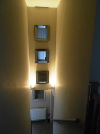Mirrors and lighting have been used to light and add interest to the stair well.