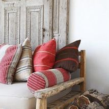 A pile of stripped cushions in similar colour's adds interest in a neutral scheme.