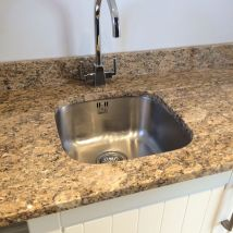 A stainless steel inset sink ith granite work top and draining grroves
