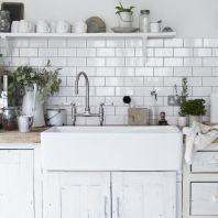 A large butler sink with tiled splash back