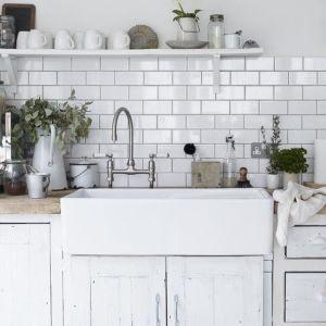 A large butler sink with tiled splashback