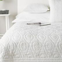 A textured white bedspread adds interest. The White Company