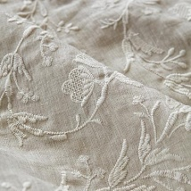 White embroidered muslin used to dress windows in a bedroom