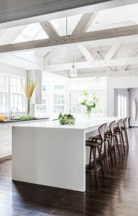 Brighter cooler whites have been used in this kitchen. Even the beams have been painted white to create a light lofty area