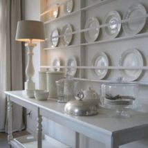 A collection of white china on white furniture is a gorgeous display