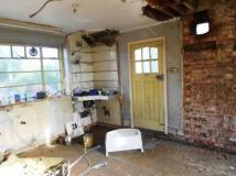 What remains of the original kitchen and a new beam and block floor has been laid and walls and chimney breast removed.