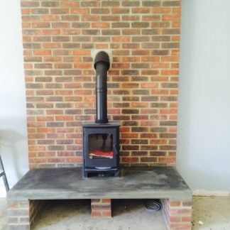 A raised hearth, brick back drop and multifuel stove in situ