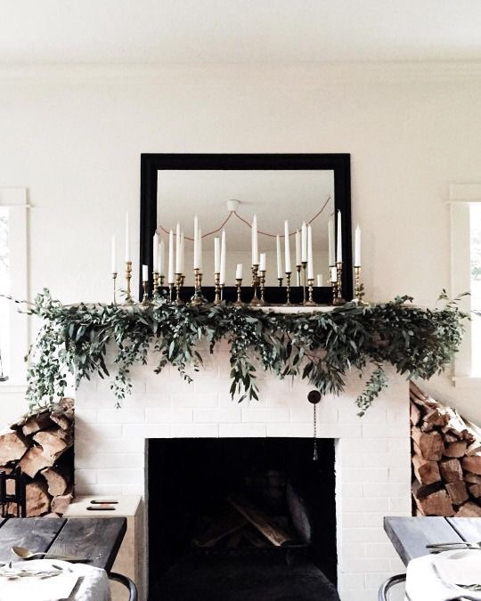 Candles and greenery for an effective hearth arrangement