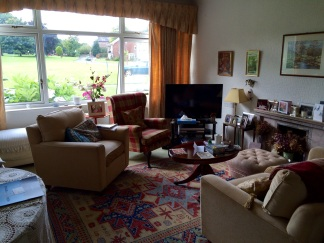 Sitting room with too much furniture and 1960's fireplace.