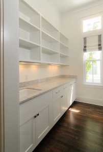 A white walk in Butlers Pantry with sink and storage