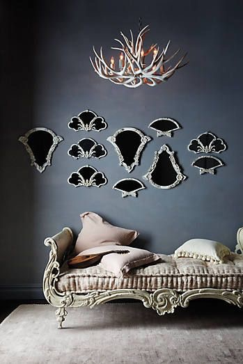 Collection of French fan mirrors displayed on wall Anthropologie