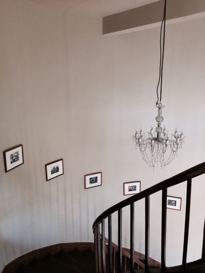 Grand staircase dressed with chandelier and modern prints