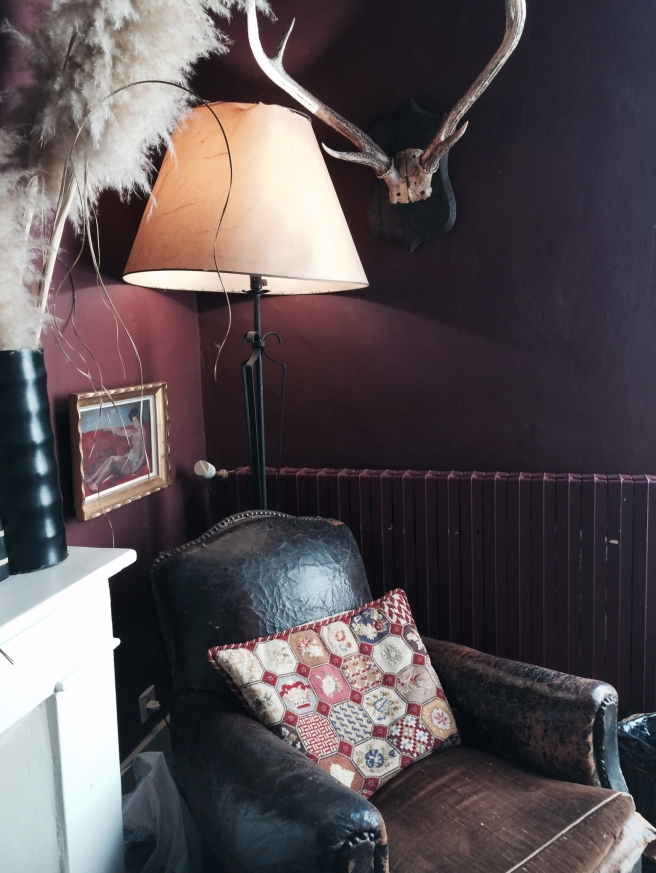 Dark red walls old leather armchair with interesting accessories makes a cosy corner