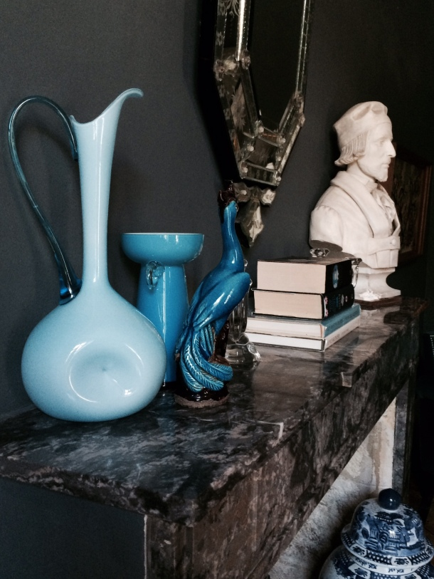 A mantle Piece styled with blue glass ornaments books and bust