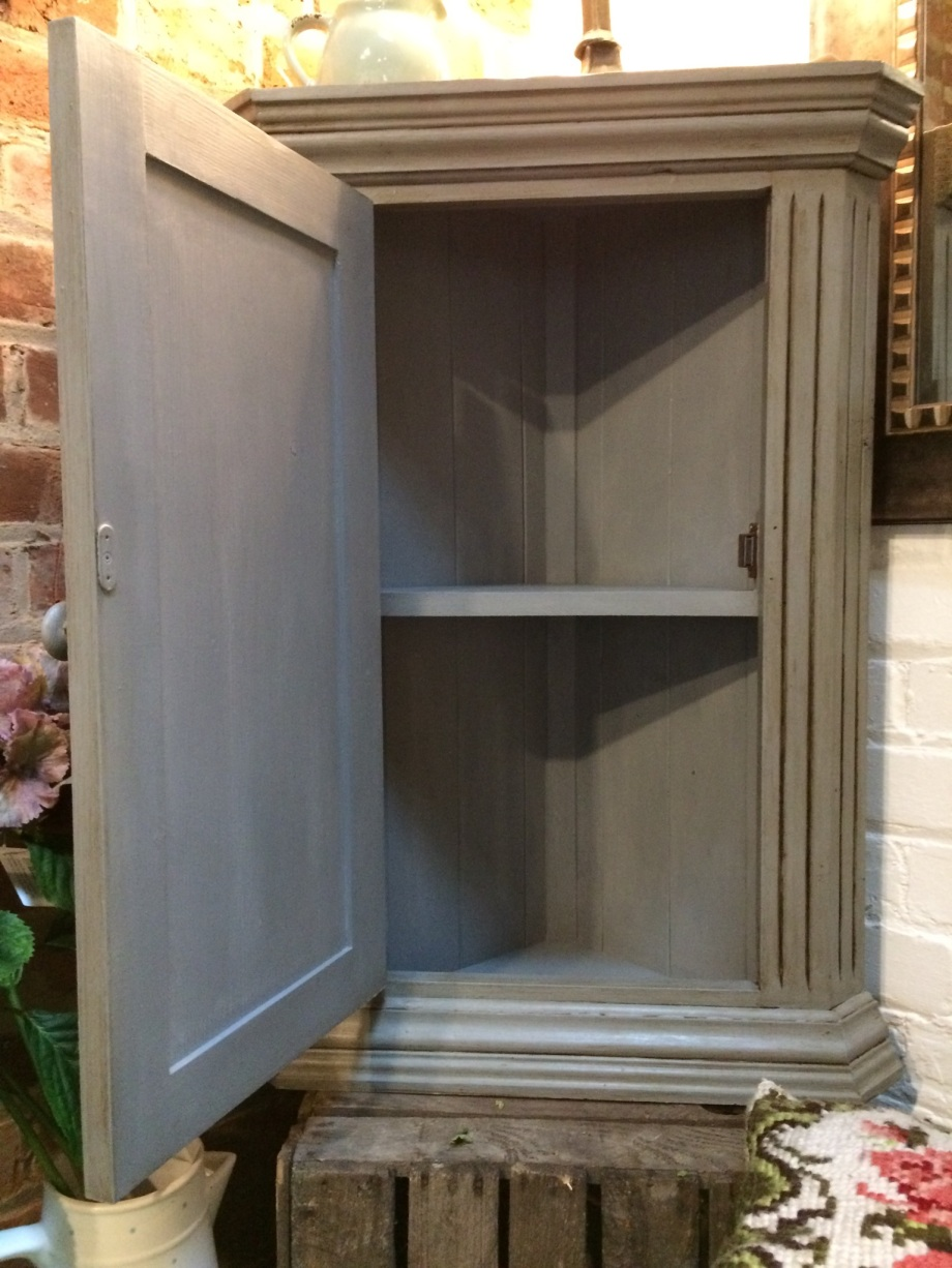 Interior of grey painted wall mounted corner cupboard