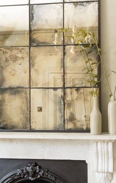 Statement antiqued mirror over fireplace