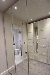 Mirrored wardrobe doors in a walk through dressing room.