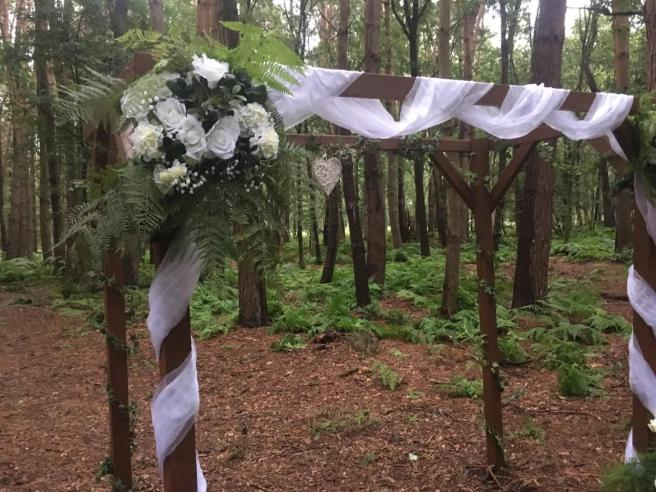 White flowers and greenery woodland wedding arch