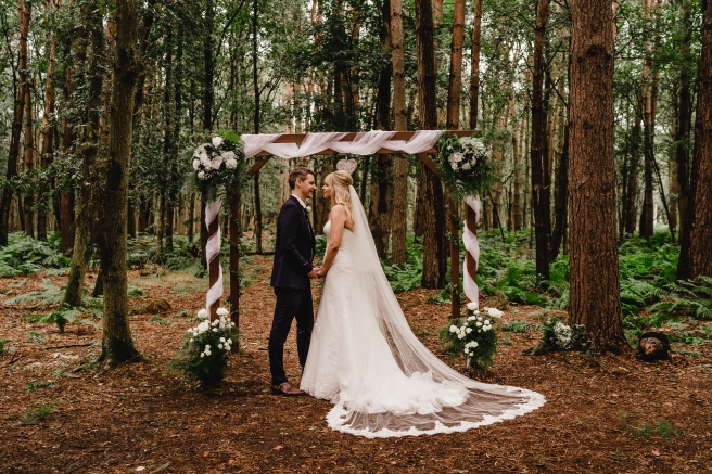 Bride and Groom by woodland wedding arch